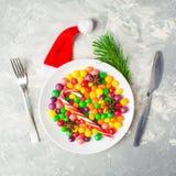 Tabla de la porción de la Navidad con platos y cubiertos y la placa de caramelos Imágenes de archivo libres de regalías