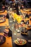 Tabla de la recepción con la decoración del partido de Halloween, los vidrios y las placas del caramelo Imagenes de archivo