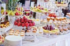 Tabla de la recepción nupcial con las diversos frutas, tortas y dulces Foto de archivo libre de regalías