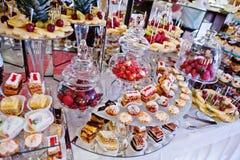 Tabla de la recepción nupcial con las diversos frutas, tortas y dulces Fotos de archivo libres de regalías