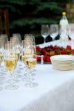 Tabla de la recepción Vidrios de vino, de champán, de placas y de bayas en el mantel blanco Negocio de abastecimiento Foto de archivo libre de regalías
