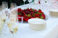 Tabla de la recepción Vidrios de vino, de champán, de placas y de bayas en el mantel blanco Negocio de abastecimiento Imagenes de archivo