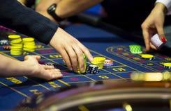 Tabla de la ruleta en manos humanas del casino foto de archivo