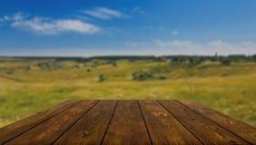 Tabla de madera al aire libre con el fondo hermoso del campo Imágenes de archivo libres de regalías