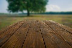 Tabla de madera al aire libre con el fondo hermoso del campo Imagenes de archivo