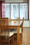 Tabla de madera, algunas sillas y ventana. Imagen de archivo libre de regalías
