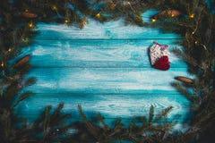 Tabla de madera azul adornada con los corazones y el árbol de navidad ligero con las guirnaldas Fotografía de archivo