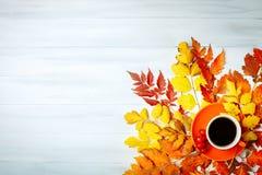 Tabla de madera blanca adornada con hojas de otoño y una taza de café Fondo del otoño con el espacio de la copia Fotos de archivo