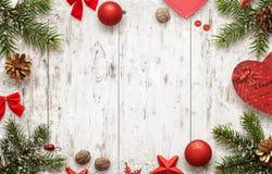 Tabla de madera blanca con la opinión superior del árbol de navidad y de las decoraciones
