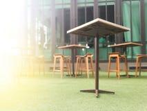 Tabla de madera borrosa y tabla de la silla en el CCB artificial de la hierba verde Fotos de archivo libres de regalías