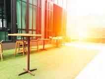 Tabla de madera borrosa y tabla de la silla en el CCB artificial de la hierba verde Imagen de archivo libre de regalías