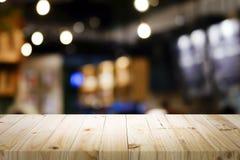 Tabla de madera con el fondo de la falta de definición de la cafetería foto de archivo libre de regalías