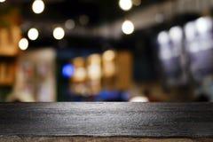 Tabla de madera con el fondo de la falta de definición de la cafetería fotos de archivo