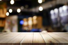 Tabla de madera con el fondo de la falta de definición de la cafetería imagen de archivo libre de regalías