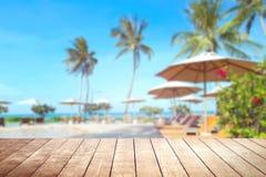 Tabla de madera con el fondo tropical borroso del mar y del centro turístico Fotos de archivo libres de regalías
