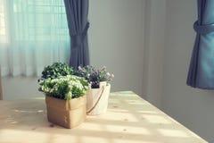 Tabla de madera con el grupo de flor artificial hermosa en el pote Fotografía de archivo libre de regalías