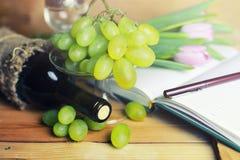Tabla de madera con el libro y la uva de la botella de vino Imagenes de archivo
