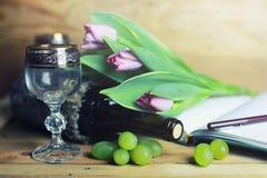 Tabla de madera con el libro y la uva de la botella de vino Fotos de archivo libres de regalías