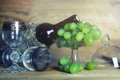 Tabla de madera con el libro y la uva de la botella de vino Imagen de archivo libre de regalías