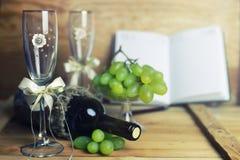 Tabla de madera con el libro y la uva de la botella de vino Foto de archivo libre de regalías