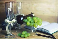 Tabla de madera con el libro y la uva de la botella de vino Imágenes de archivo libres de regalías