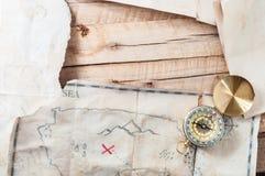Tabla de madera con el mapa de papel y antiguo envejecido vintage del tesoro con el compás Con el espacio para su diseño Imagen de archivo