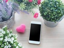 Tabla de madera con el marco hermoso de la flor en el pote y la pantalla en blanco f Fotografía de archivo libre de regalías