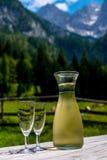 Tabla de madera con el vino en el fondo de montañas Foto de archivo libre de regalías