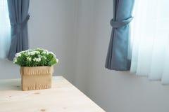 Tabla de madera con la flor blanca hermosa en el pote Foto de archivo libre de regalías