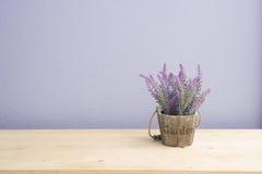 Tabla de madera con la flor púrpura de la lavanda en la maceta y la pared púrpura del cemento Fotografía de archivo