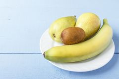 Tabla de madera con la fruta orgánica madura en la placa blanca Fruta de las peras, del plátano y de kiwi para el desayuno o la c Imagen de archivo libre de regalías