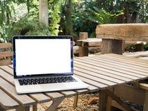 Tabla de madera con la pantalla en blanco en el ordenador portátil en el parkland imagen de archivo libre de regalías