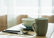 Tabla de madera con la taza y plato en sitio dinning moderno Imágenes de archivo libres de regalías