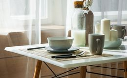 Tabla de madera con la taza y plato en sitio dinning moderno en casa Foto de archivo