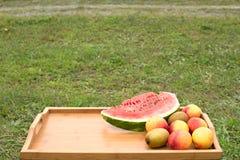 Tabla de madera con las frutas en un fondo de la hierba verde Imagen de archivo