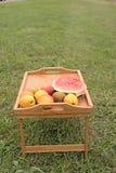 Tabla de madera con las frutas en un fondo de la hierba verde Foto de archivo