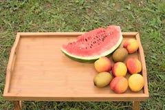 Tabla de madera con las frutas en un fondo de la hierba verde Fotografía de archivo