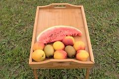 Tabla de madera con las frutas en un fondo de la hierba verde Imágenes de archivo libres de regalías