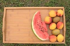 Tabla de madera con las frutas en un fondo de la hierba verde Fotos de archivo