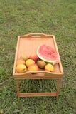 Tabla de madera con las frutas en un fondo de la hierba verde Fotografía de archivo libre de regalías