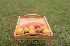 Tabla de madera con las frutas en un fondo de la hierba verde Foto de archivo libre de regalías