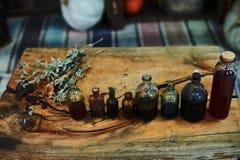 Tabla de madera con las hierbas secadas, botellas, una visión superior, en el estudio, por la tarde Fotos de archivo libres de regalías