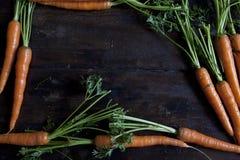 Tabla de madera con las zanahorias Escriba un menú Fondo negro imágenes de archivo libres de regalías