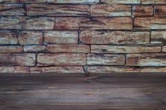 Tabla de madera con un haz de luz cerca de la pared de ladrillo vieja foto de archivo