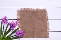 Tabla de madera de Pascua adornada con las flores púrpuras, sobre la visión superior Imagen de archivo libre de regalías