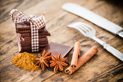 Tabla de madera del chocolate rodeada por las especias Fotos de archivo