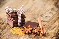 Tabla de madera del chocolate rodeada por las especias Fotografía de archivo libre de regalías