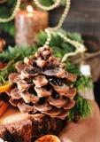 Tabla de madera del cono de abeto con las decoraciones de la Navidad y de la Navidad, foco selectivo Foto de archivo