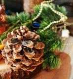 Tabla de madera del cono de abeto con las decoraciones de la Navidad y de la Navidad, foco selectivo Imagen de archivo libre de regalías
