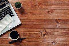 Tabla de madera del escritorio de oficina con el ordenador port?til, la taza de caf? y las fuentes foto de archivo